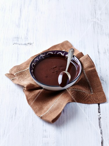 A bowl of melted chocolate and a spoon
