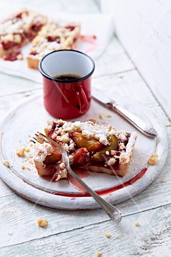 A slice of plum cake with coconut crumbles and a mug of coffee