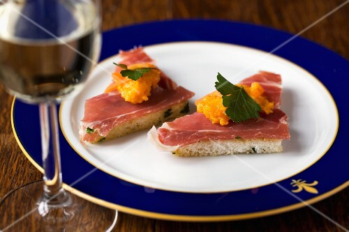 Toast triangles topped with smoked ham and carrot cream