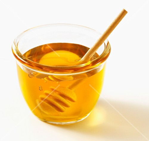 Honey in a glass bowl with a wooden spoon