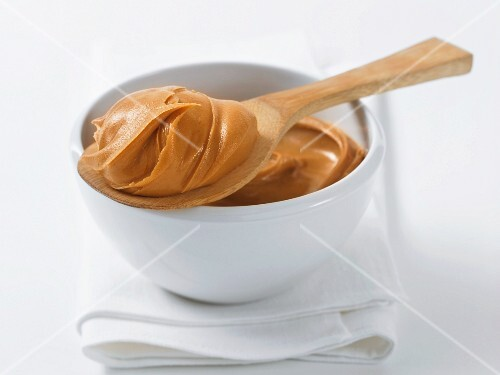 Peanut butter in a bowl and on a wooden spoon