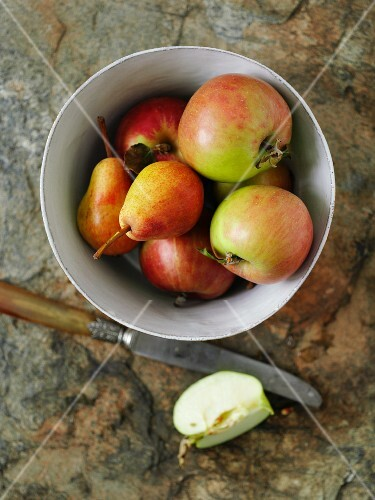 A bowl of apples and pears with a knife and an apple wedge next to it