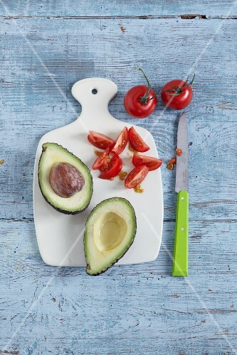 A halved avocado and tomatoes on a chopping board