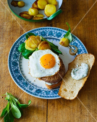 A fried potato burger with a fried egg and lamb's lettuce