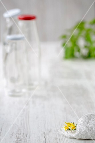 Empty glass bottles, tomato leaves and a kitchen cloth on a wooden surface