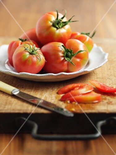 Tomatoes on a white plate and a sliced tomato on a wooden board