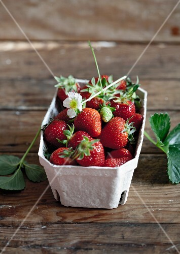 Strawberries with leaves and flowers in a cardboard punnet