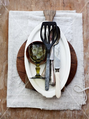 Various kitchen utensils, crockery, cutlery and a wine glass on a linen cloth