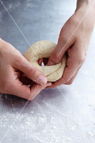 Dough being shaped into a bagel