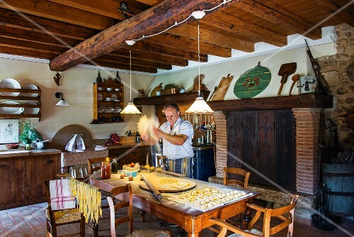 Mario Zini making fresh pasta in the kitchen of his rustic country house