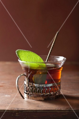 A glass of black tea with a sage leaf