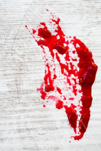 A red jam stain on white wood