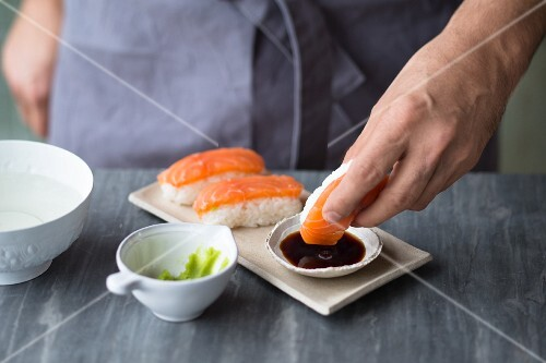 Nigiri sushi with salmon being dipped in soy sauce and wasabi paste