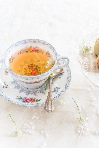 Tea in a floral-patterned cup next to macaroons