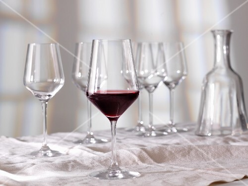 A half full glass of red wine in front of empty glasses and a caraffe