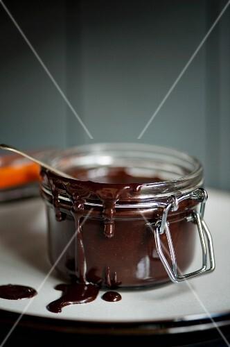 An open jar of chocolate fudge sauce on a plate