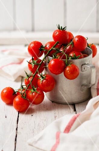 Freshly washed vine tomatoes in a tin mug