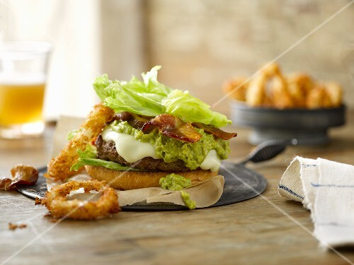 A cheeseburger with cheddar, guacamole, bacon, iceberg lettuce and crispy onion rings
