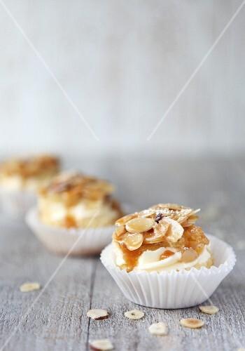 Three Bienenstich muffins (caramelised almond cake) on a wooden surface