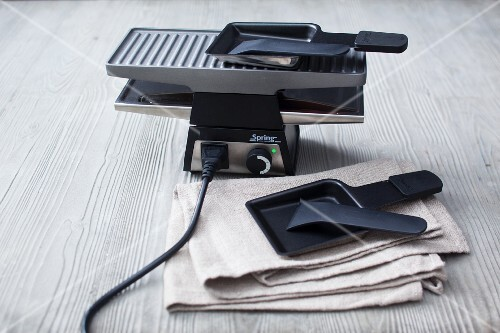 A raclette machine for two with two pans