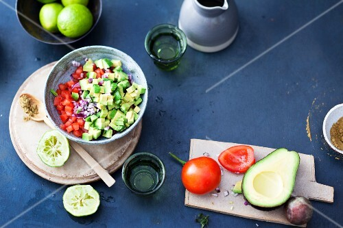 Avocado and tomato salsa being made to be served with raclette