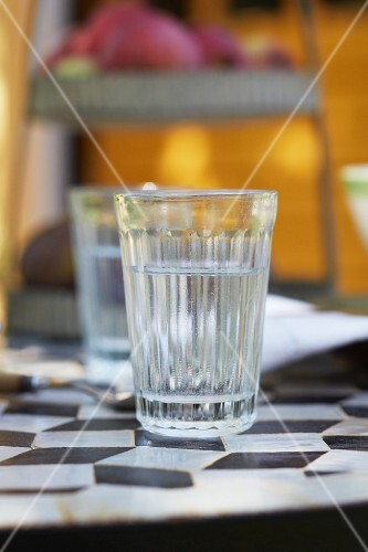 A glass of water on a French bistro table with a black and white diamond pattern