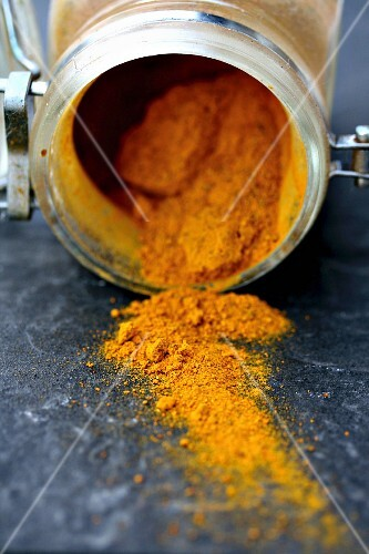 Turmeric powder in an opened glass jar