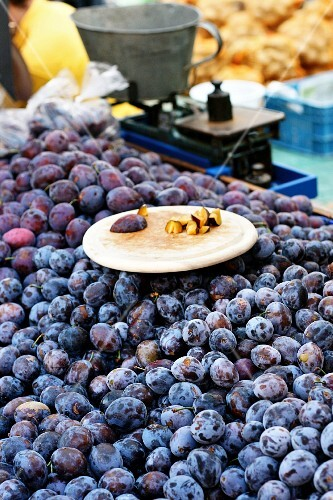 Fresh damsons at a market with pieces on a wooden board to taste