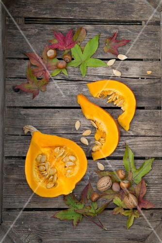A slice and wedges of a Hokkaido pumpkin on a wooden surface with autumnal decorations