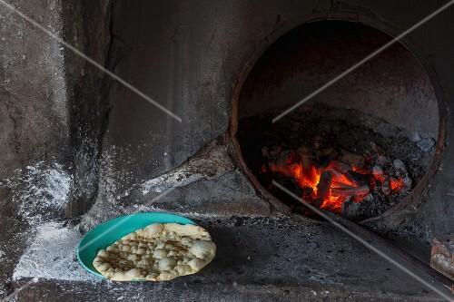 Unleavened bread in front of a bakery oven (Yangon, Myanmar)