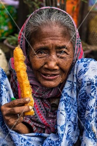 Alte Burmesin isst frittiertes Gebäck zum Frühstück (Yangon, Myanmar)
