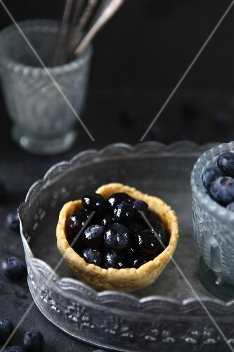 Pudding tartlet with blueberries on a pewter tray