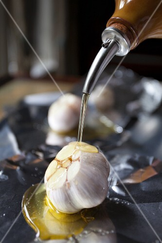 A bulb of garlic being drizzled with olive oil