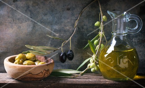 Green olives in an olive wood bowl, and olive sprig and a carafe of olive oil