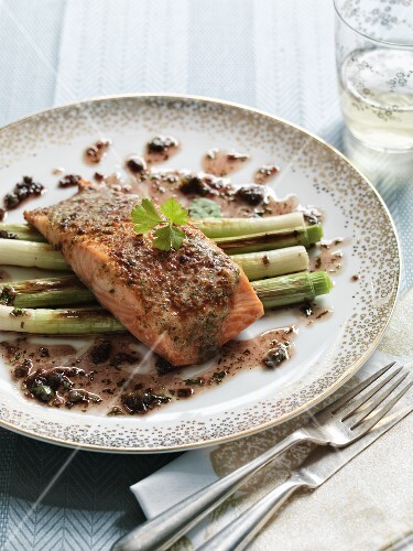Salmon with a nut and herb coating and red wine sauce on a bed of spring onions