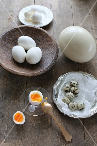 A soft-boiled egg in an egg cup with an egg spoon on a wooden table