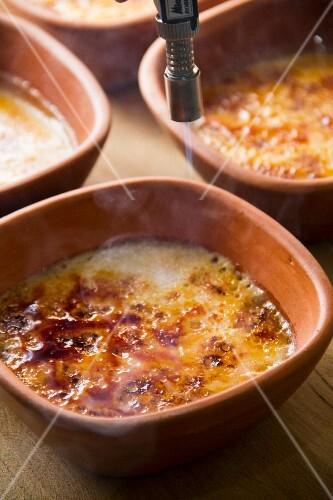 Crème brûlée being caramelised with Bunsen burner