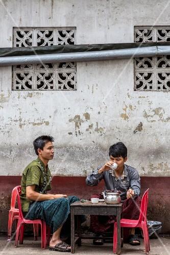 Two men drinking tea in front of a cookshop in Yangon, Myanmar