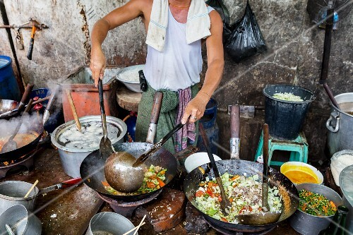 A rustic cookshop with a man cooking at a large wok