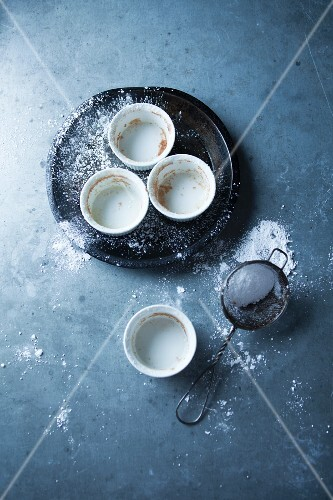 Empty baking tins and a sieve of icing sugar