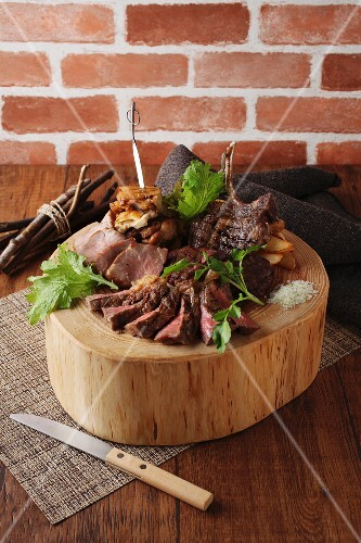 Sliced roast beef with chips on a round wooden block