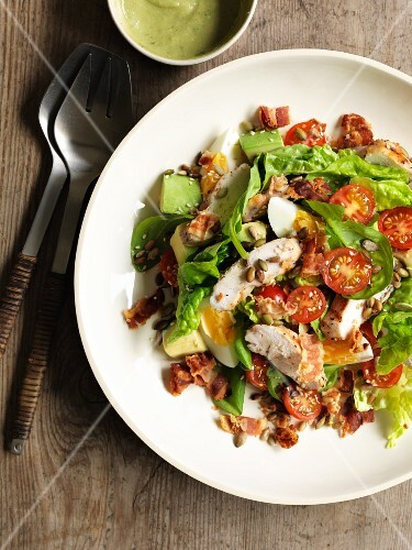 A mixed salad with avocado, egg, tomatoes, bacon and chicken breast