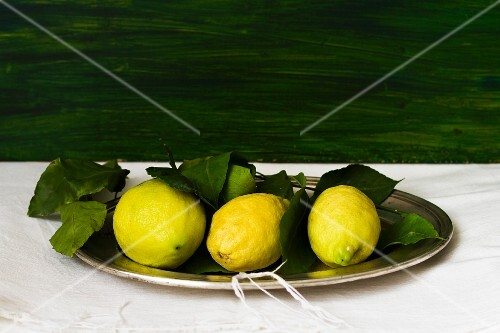Three lemons with leaves on a tray