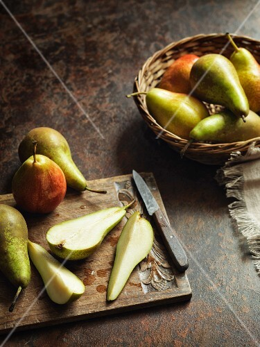 An arrangement of whole and sliced pears