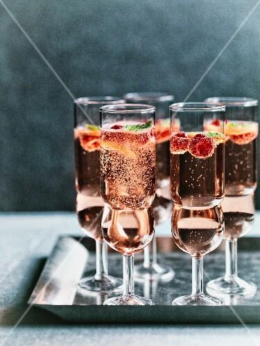 Glasses of rosé raspberry mint fizz on a metal tray