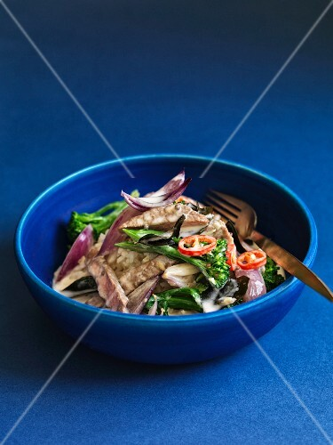 Pork with rice and vegetables in a blue bowl