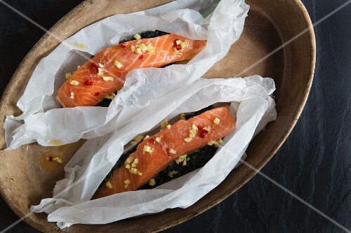 Raw salmon fillets in paper with ginger and chilli