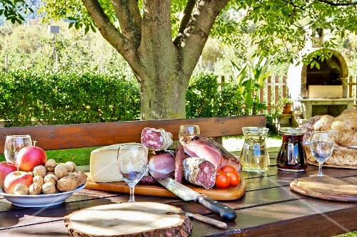 A sumptuous supper platter, a basket of bread, fruit and nuts on a garden table