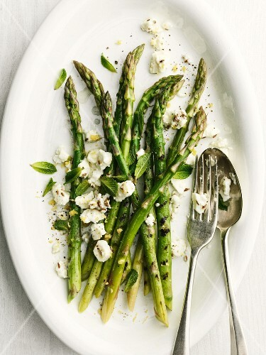 Grilled green asparagus with sheep's cheese and cutlery