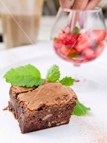 A chocolate brownie with marinated strawberries